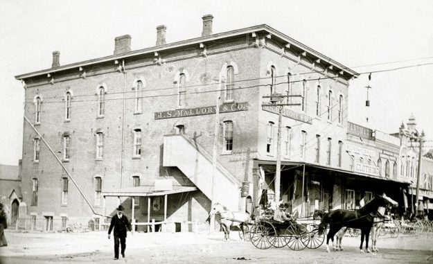 "Building known as both the Rininger block and the Horr block, which burned in 1915. Formerly located on the northern corner of Main Street and Mechanics Street (now East Herrick Avenue). Image must have been taken after 1882, as the tin cornice of the second Rininger store is visible on the right side. Photo courtesy of the Southern Lorain County Historical Society, ""The Spirit of '76"" Museum."
