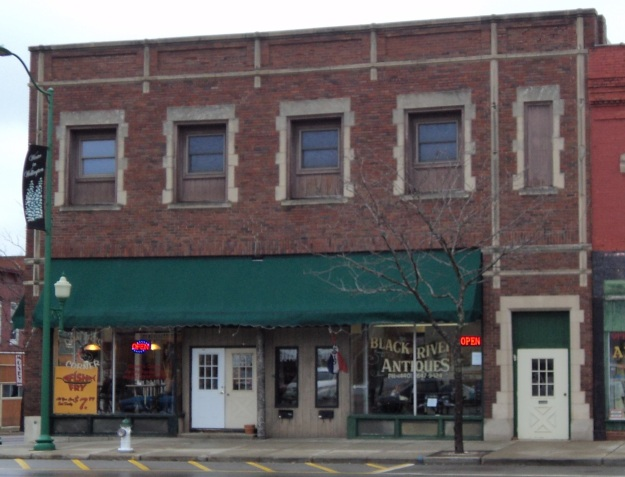 The two-story building that replaces the Rininger or Horr Block, currently standing on the northeast corner of Main Street and Herrick Avenue. Photo by author.
