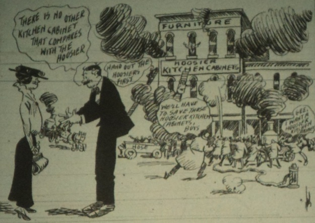"Detail of an advertisement for E.E. Watters' store, featuring a cartoon depiction of the Horr Block burning as firemen rush to save valuable Hoosier Kitchen Cabinets (the items being promoted). ""The Wellington Enterprise,"" 6-9-1915, pg. 1. Photo by author."